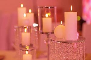 Burning candle in a round glass candlestick with decorative seashells. Candles on a glass candlestick photo