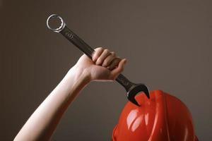 llave grande en la mano de la mujer. mano sostiene una llave sobre un fondo gris. llave combinada. llave grande de cromo vanadio en la mano. trabajo de mujeres. foto