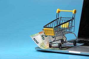 carro de la compra en miniatura, unos billetes de cincuenta euros en un ordenador portátil sobre fondo azul. concepto de compras en línea y comercio electrónico. foto