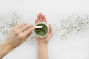 Young female hands using green natural cream for face or body. Organic natural skincare products and flowers on white background. Packaging of lotion or cream. Beauty cosmetic skincare concept photo
