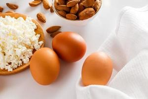 Eggs, cheese, and nuts on white background photo