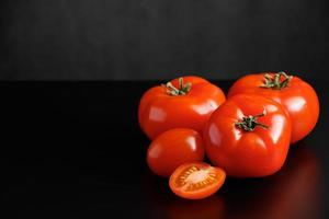 tomates rojos maduros sobre un fondo negro foto