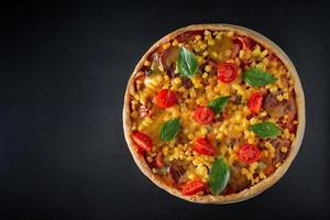 Gran pizza italiana con tomates y albahaca sobre un fondo negro foto