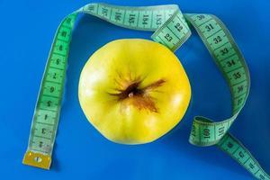 frutas y cintas métricas sobre un fondo azul foto
