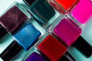 Group of bright colored nail polishes on blue background photo