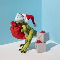 Silly Christmas dinosaur holding gifts photo