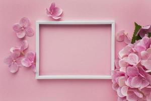 Empty white frame on pink background with flowers