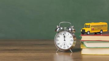 Despertador y autobús escolar en escritorio de madera foto