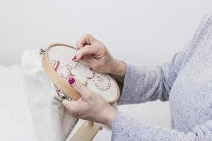 Woman's hand cross-stitching pattern on a hoop against a white background. Resolution and high quality beautiful photo