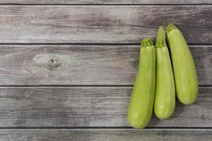 Fresh zucchini on wooden background photo
