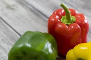 Red, green, and yellow pepper, on a wooden table. photo