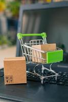 Close-up of a shopping cart with a box, next to a laptop and credit card, on the desk. photo