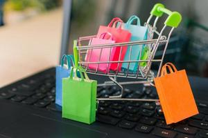 Colored paper shopping bags in shopping cart on a laptop computer keyboard. Online shopping from sites via the internet concept. photo