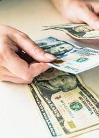 Woman's hands counting dollar bills on white desk photo