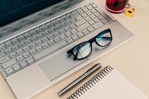 Business composition with laptop, glasses, fountain pen, and notebook on a work desk. photo