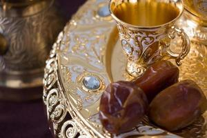 Still life with traditional golden Arabic coffee set with dallah, coffee pot, jezva, cup, and dates. Dark background. Horizontal photo