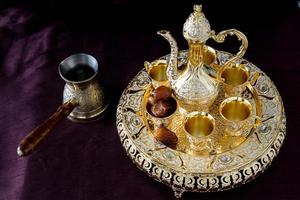 Still life with traditional golden Arabic coffee set with dallah, coffee pot, and dates. Dark background. Vertical photo