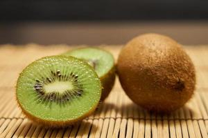 Ripe brown kiwi and cutted green kiwi close up on a straw background.
