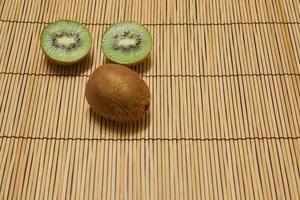 kiwi marrón maduro con kiwi verde cortado sobre un fondo de paja con espacio para texto. foto