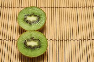 kiwi cortado verde maduro sobre un fondo de paja con espacio para texto. foto