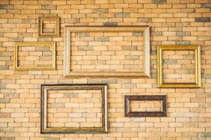 Blank photo frames on brick wall