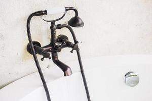 Old vintage faucet on bathtub photo