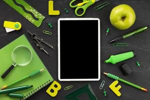 Green school supplies arrangement with mock up tablet on black background