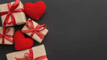 Brown wrapping paper gifts with red ribbon and crotched hearts photo