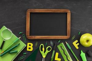 Green school supplies arrangement with blank chalkboard on black background