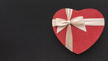 Heart shaped gift box on black background photo