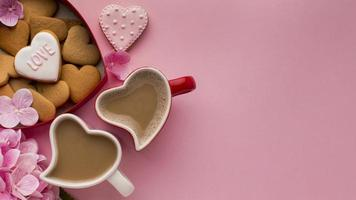 Heart shaped mugs and cookies on pink background photo