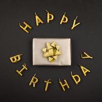 velas de feliz cumpleaños y regalo sobre fondo negro foto