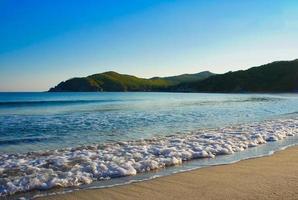 Olas en la playa y las montañas de fondo en el mar de Japón foto