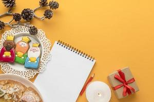 Escritura de carta a santa con galletas navideñas, fondo amarillo foto