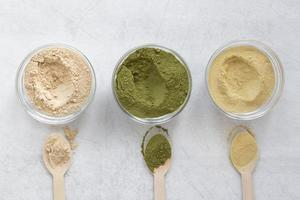 Matcha and nutritional powders in bowls on neutral background photo