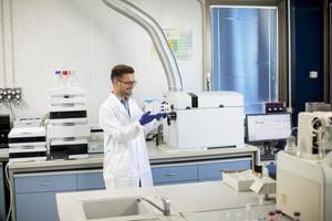 Joven investigador trabajando con muestras químicas en laboratorio con sistema HPLC y equipo de cromatografía foto