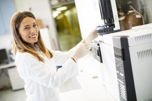 Investigadora en una bata de laboratorio blanca poniendo un frasco con una muestra para un análisis en un cromatógrafo de gases en el laboratorio biomédico foto
