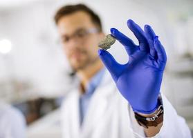 Joven científico sostenga un espécimen mineral en un guante protector en el laboratorio de ciencia de materiales foto