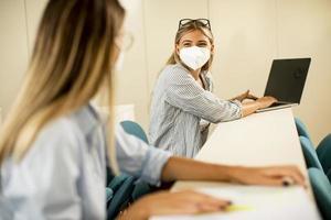 Estudiante con máscara médica protectora facial para protección contra virus en la sala de conferencias foto