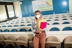 Estudiante con máscara médica protectora facial para protección contra virus de pie en la sala de conferencias foto