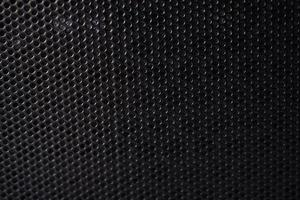 Black background made of iron grating with small round holes photo