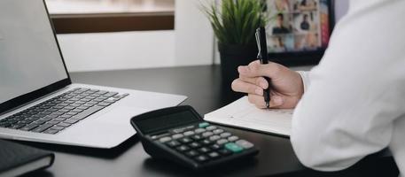Tomando notas profesionales con calculadora y portátil en la mesa. foto