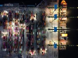 Jakarta, Indonesia 2021- Aerial view of Container ship loading and unloading in deep sea port, logistic import and export freight transportation by container ship in open sea at night