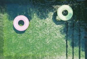 Green bottom pool seen from above with pink and green floats and palm tree shadows, 3d render photo