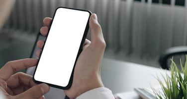 Person holding a smartphone at a desk mock-up photo