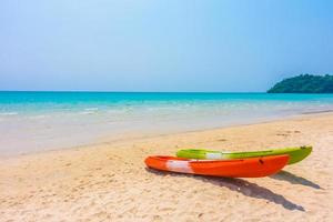 Colorful kayak boat on beach and sea photo