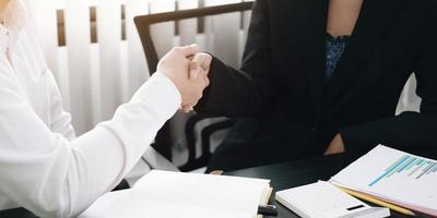 Two professionals shaking hands at a desk photo