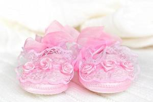 Pink baby booties on white crochet blanket. photo