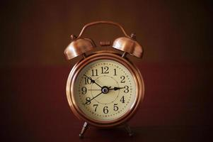 Alarm clock on a dark brown background photo