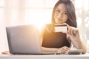 Woman holding credit card in front of a laptop photo